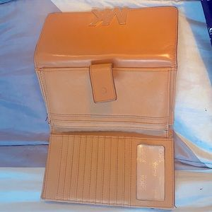 This is a tan 8 inch Michael Kors hand held wallet